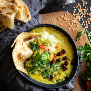 Bowl filled with coconut lentils topped with cilantro, chilis, pomegranate and paratha