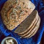 overhead shot of no-knead Dakota Bread on a blue cloth