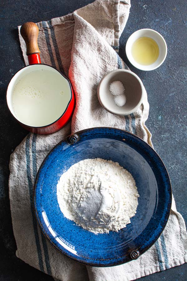 Bowl of flour with a pan of milk, bowls with salt, sugar and oil