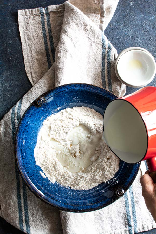 Small pan with warm milk pouring on top of paratha ingredients