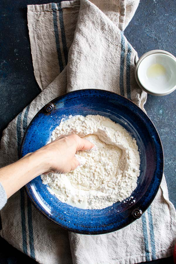 A hand mixing a bowl of paratha ingredients and warm milk