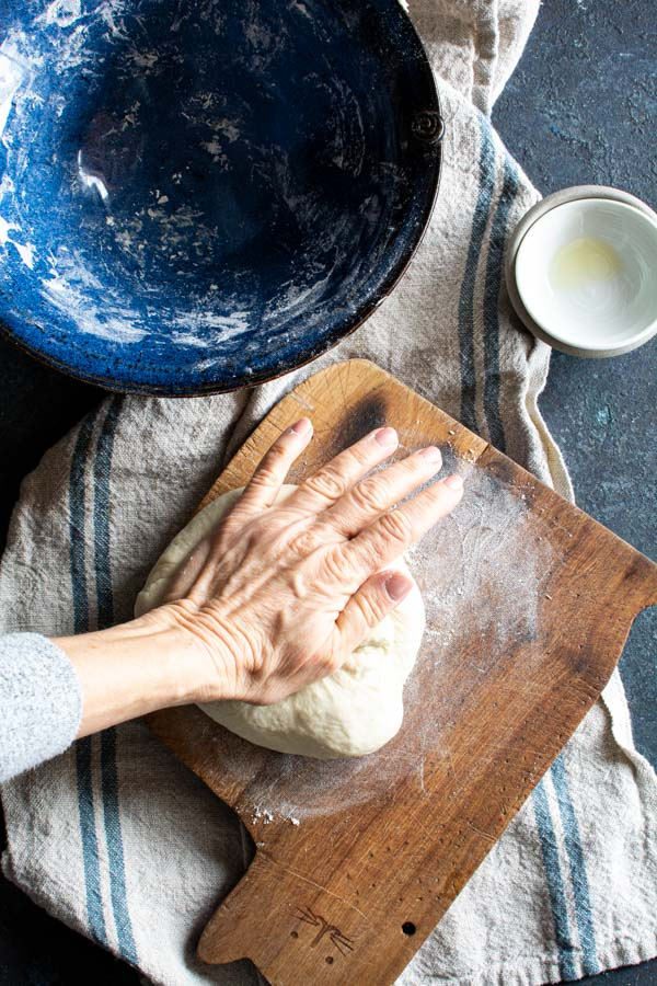 Paratha dough being kneaded by hand on a wooden board