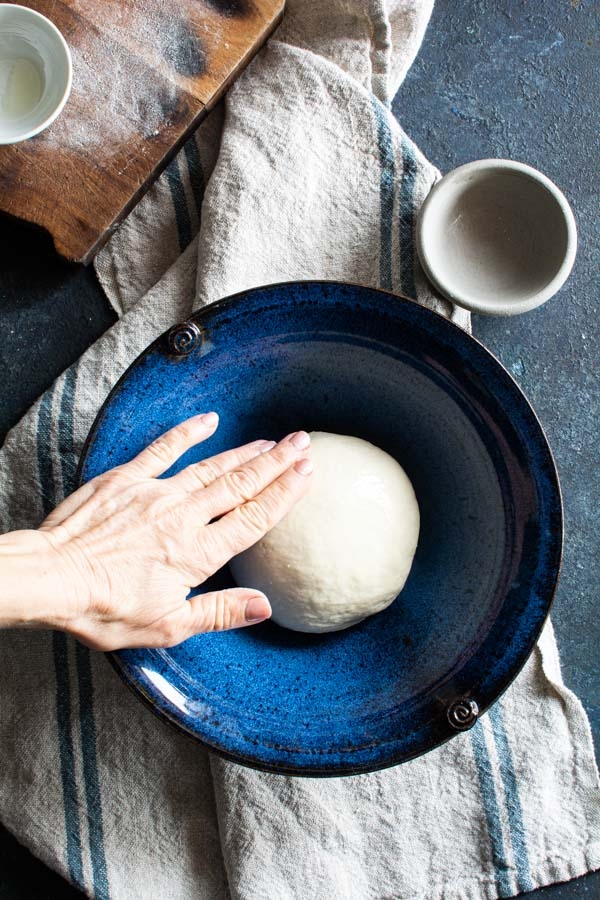 Round ball of paratha dough in a large bowl being oiled by hand