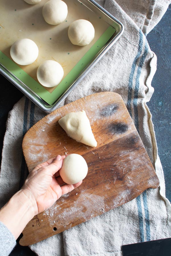 Segments of paratha dough rolled into balls placed on baking sheet