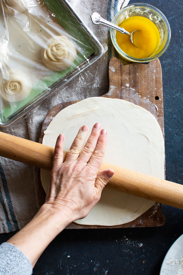 Rolling pin rolling out flattened disk of paratha dough