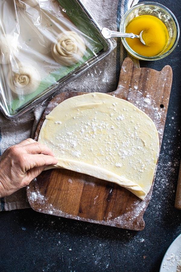 Paratha dough being folded like a fan on floured board