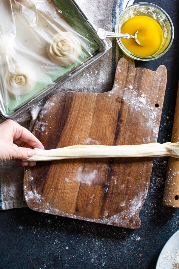 Hand stretching strip of paratha dough on a floured board
