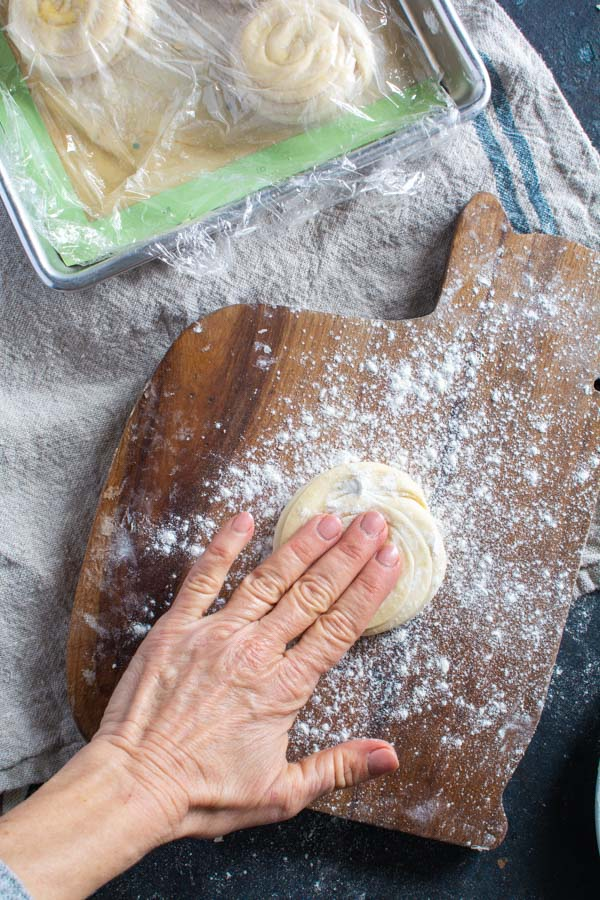 Hand pressing layered paratha dough in floured board.