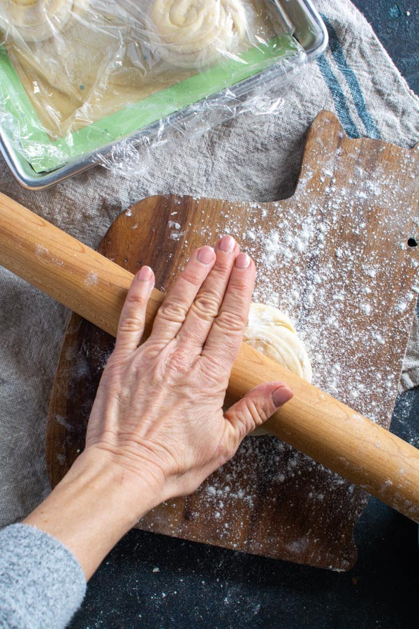 Hand on rolling pin rolling out paratha