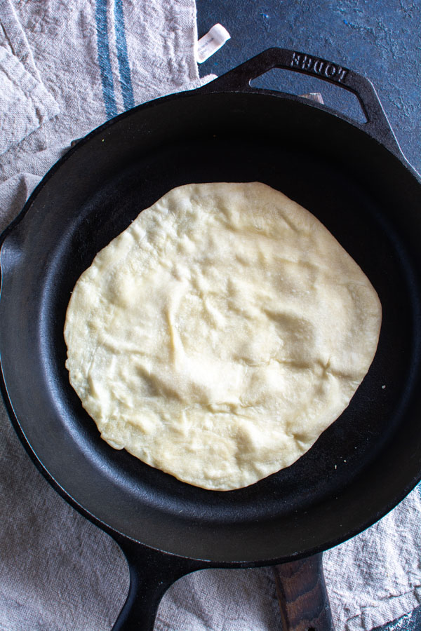 large black cast iron skillet with one paratha cooking