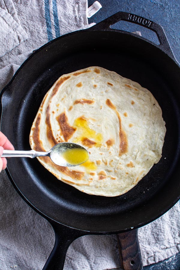 Cooked paratha in cast iron skillet with ghee drizzled on top