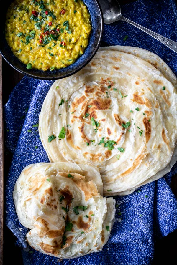 Flakey Paratha flat bread stacked on a cloth with a bowl of lentils