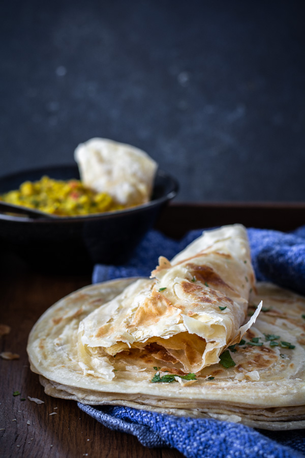 Stack of flakey paratha with bowl of lentils in background