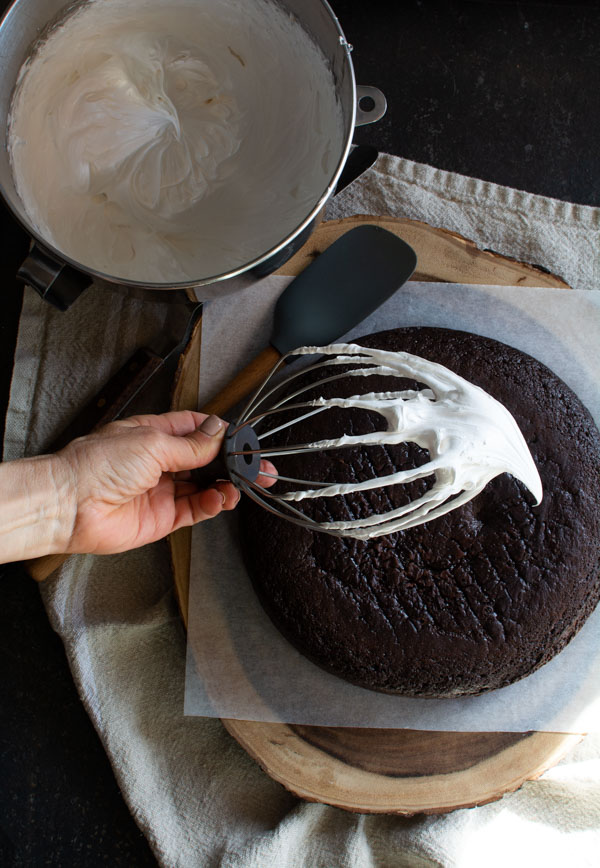 Round chocolate devil's food cake on a wooden board with a whisk of boiled icing dripping off.