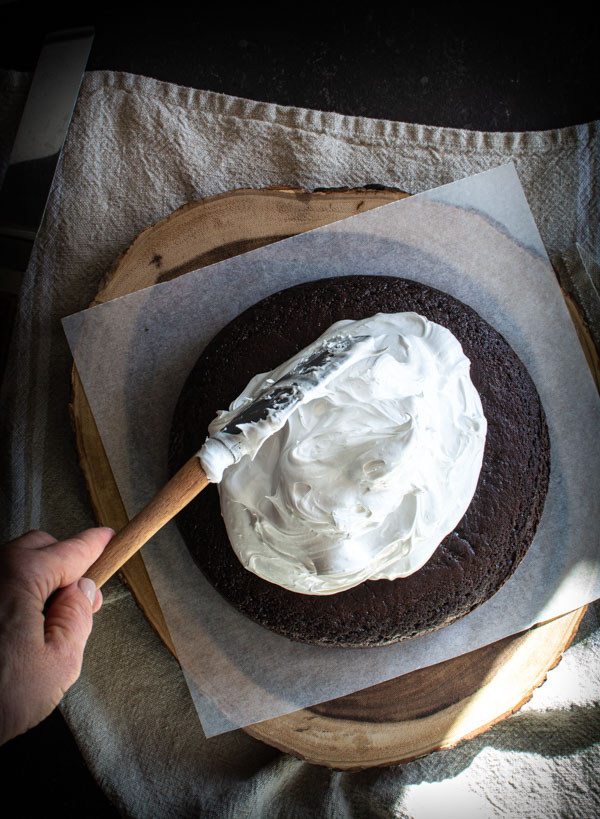 Large pile of boiling icing on top of a round devil's food cake