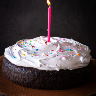 Lit candle on top of Old Fashioned Devil's Food Cake with Boiled Icing