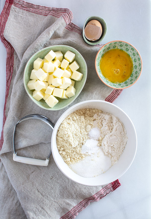 crumble ingredients in a bowl with butter cubes and an egg