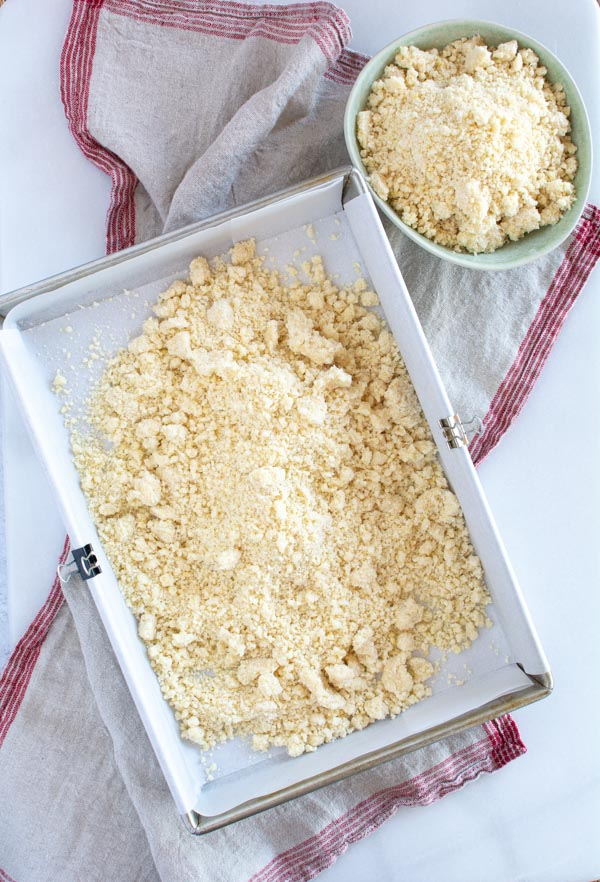 Parchment lined baking pan with crumble mixture