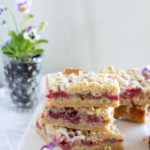 Stacked Strawberry Rhubarb Almond Crumble Bars on a white cloth