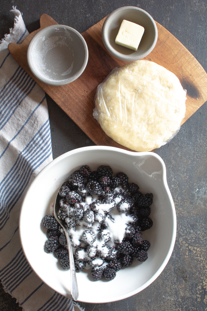 Blackberries with sugar in large bowl with sugar, butter and pie dough on cutting board