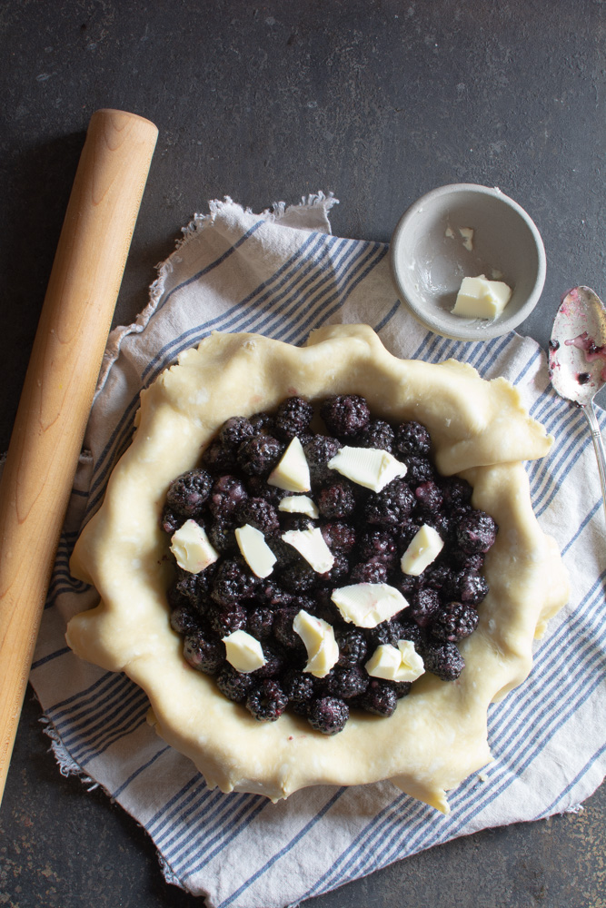 Pie dough filled with blackberries dotted with butter
