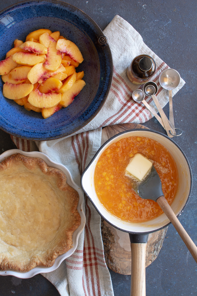 A bowl of fresh sliced peaches, baked pie shell, and a pot with peach glaze with a pat of butter.
