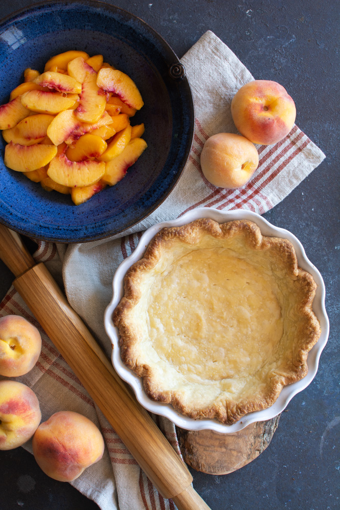 A bowl of peaches next to a baked pie shell