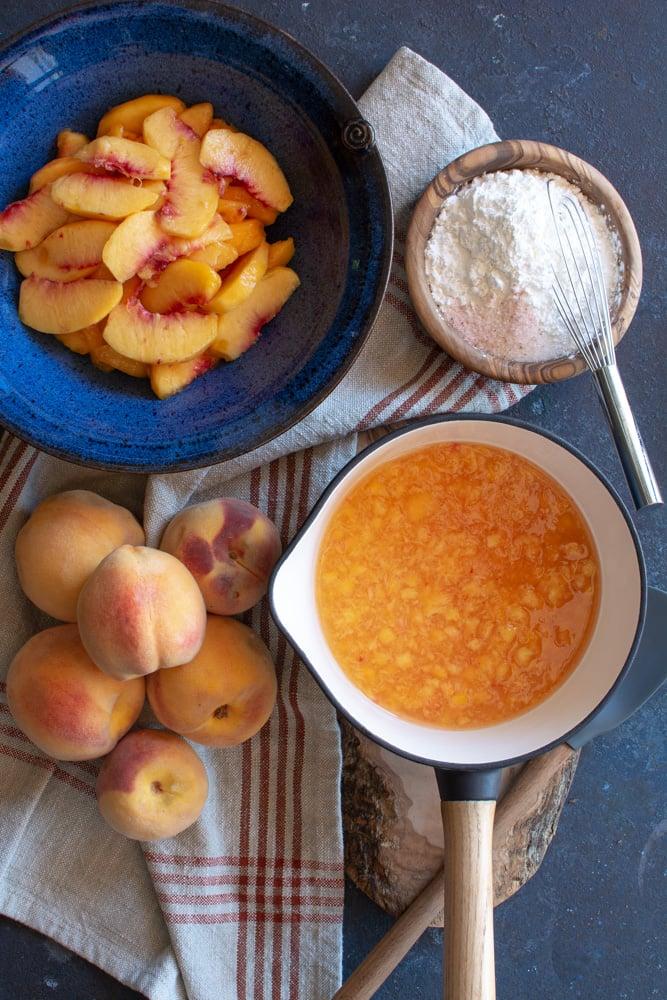 A bowl of sliced peaches, a bowl of sugar and cornstarch mixture, 5 peaches next to a pot of peach glaze.