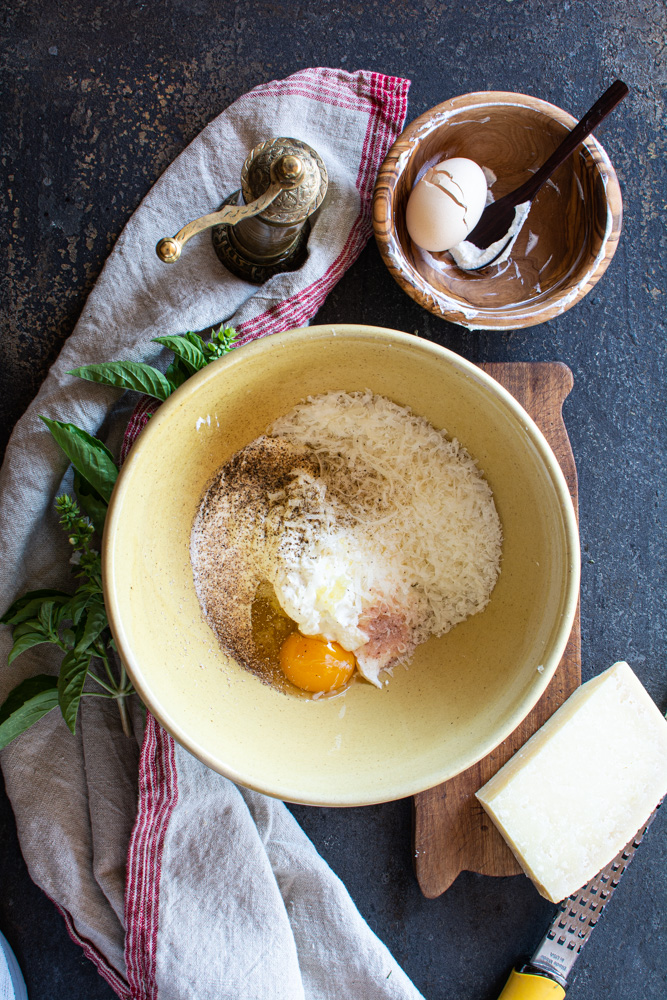 Yellow bowl with ricotta, parmesan, eggs, salt and pepper