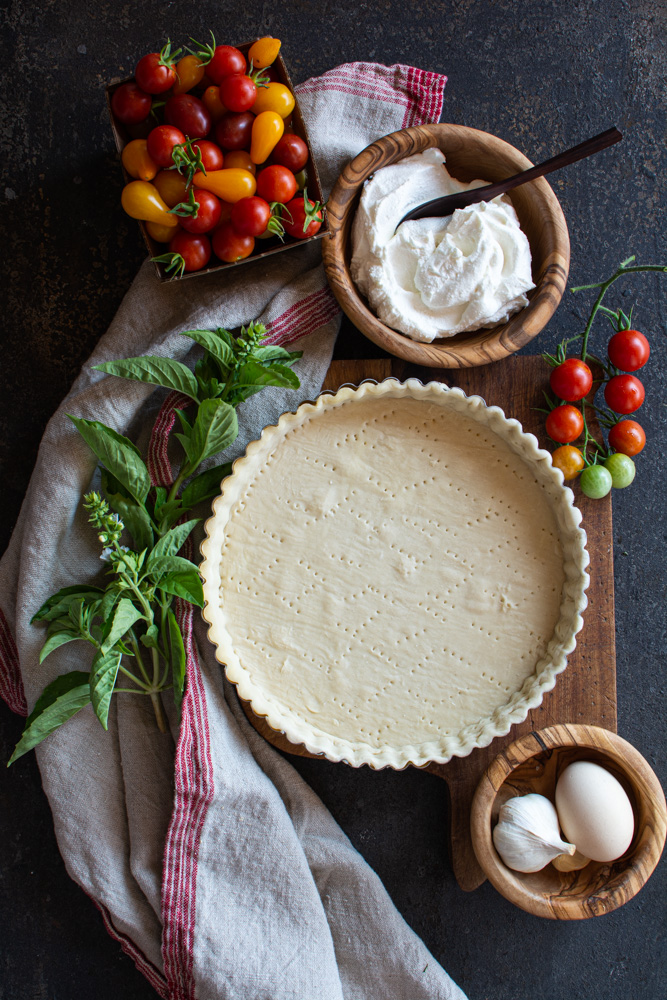 Pastry lined tart pan with fresh basil, ricotta, eggs, garlic and cherry tomatoes