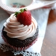 chocolate cupcake with strawberry icing with whole strawberry on top