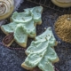 Tree cut out sugar cookies with green icing and golden sprinkles