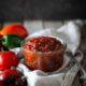 Jar of tomato jam on a linen towel with tomatoes and jalapeno peppers scattered