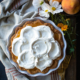 Fresh peach pie topped with whipped cream.